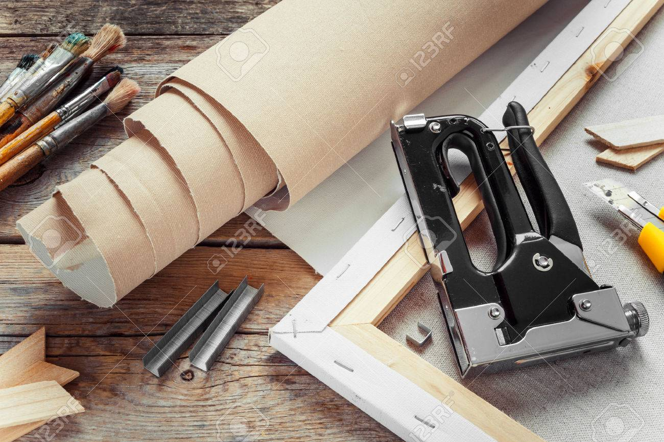 33810489-artist-canvas-in-roll-canvas-stretcher-staple-gun-and-paintbrushes-on-old-table
